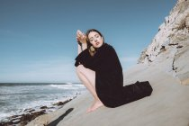 Young brunette in black coat sitting on coastline with closed eyes — Stock Photo