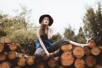 Mulher elegante de chapéu posando na pilha de log — Fotografia de Stock