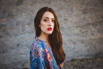 Femme brune aux lèvres rouges, marchant sur un terrain rocheux et regardant la caméra — Photo de stock