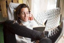 Женщина в гамаке расслабляется с книгой — стоковое фото