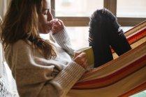 Женщина курит и лежит в гамаке с чашкой в руке — стоковое фото