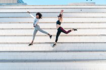 Pretty fit women jumping on steps at urban park — Stock Photo