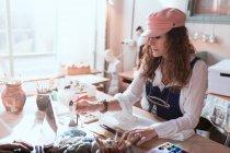 Зрелые художник с кистью на столе в мастерской — стоковое фото