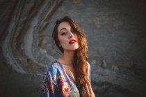 Брюнетка в платье, позирующая против камней — стоковое фото