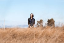 Man posing on dry field at sunny day — Stock Photo