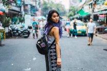 Mulher com cabelo roxo posando na rua e olhando sobre o ombro para a câmera — Fotografia de Stock