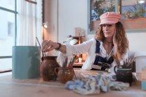 Fröhliche Maler Pinsel am Tisch im Workshop setzen — Stockfoto