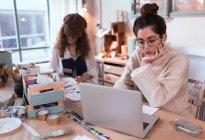 Mulher morena no laptop em oficina — Fotografia de Stock