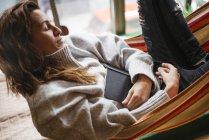 Жінка, що спить у гамаку з книгою — стокове фото
