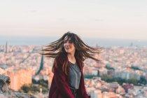 Souriante brunette cheveux ondulant sur la colline à la lumière du coucher du soleil — Photo de stock