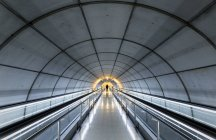 Unrecognizable person standing in empty tube with moving walkways. — Stock Photo