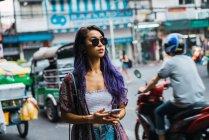 Jeune femme à lunettes de soleil avec le smartphone en mains sur la rue de la ville. — Photo de stock