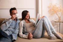 Joven pareja alegre sentados en el sofá juntos y utilizando la tableta . - foto de stock