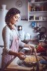 Seitenansicht einer lächelnden Frau in der Küche — Stockfoto