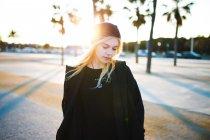 Молодая красивая блондинка в черной одежде ходит по бульвару в солнечный день . — стоковое фото