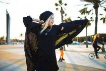 Блондинка в теплой куртке позирует на бульваре в солнечный день . — стоковое фото