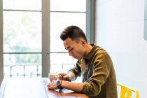 Portrait of young man drinking coffee and browsing smartphone — Stock Photo