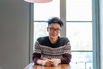 Cheerful young man drinking coffee at atble — Stock Photo