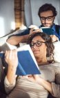 Couple lying on couch at home and reading books — Stock Photo