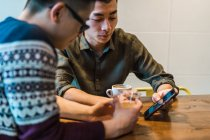 Junge Freunde chillen im Café und surfen auf dem Smartphone — Stockfoto