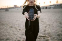 Crop blonde woman on sand with camera — Stock Photo