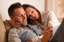 Joven pareja cariñosa acostados juntos y utilizando ficha - foto de stock