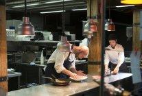 Cooks preparing dishes in restaurant kitchen — Stock Photo