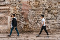 Side view of two young men walking one by one against stone wall on street. — Stock Photo