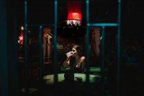 Молодая женщина сидит и пили пиво, один в пустой бар ночью — стоковое фото