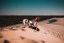 Donna allegra con piccolo cane seduto sulla sabbia nella giornata di sole . — Foto stock