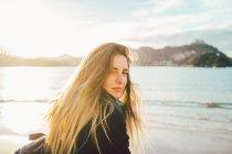 Verträumtes Mädchen steht am Sandstrand und blickt über die Schulter in die Kamera — Stockfoto