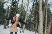Uomo felice che porta la ragazza sul retro nella foresta invernale . — Foto stock