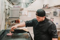 Chef turning and cooking patty at restaurant kitchen — Stock Photo