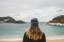 Rear view of girl in hat posing over ocean bay — Stock Photo