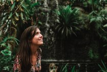 Side view of smiling brunette girl on background palm trees — Stock Photo