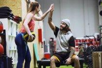Fröhlichen sportlichen Mann und Frau geben hohe fünf während des Trainings in der Turnhalle — Stockfoto