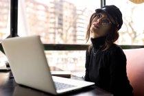 Stylish young girl sitting at laptop and looking at camera — Stock Photo