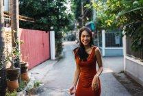 Веселая женщина в красном платье ходит по улице — стоковое фото