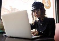 Femme élégante, assis au café et navigation sur ordinateur portable — Photo de stock