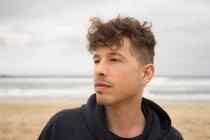 Человек позирует на песчаном пляже в облачный день . — стоковое фото