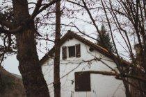 Außenseite des Landhaus durch kahle Äste gesehen — Stockfoto