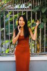 Cheerful woman in red dress posing by fence at street — Stock Photo