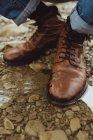 Чоловічий ноги в коричневої шкіри чоботи в калюжу — стокове фото