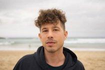 Молодой человек смотрит в камеру на песчаном пляже в пасмурный день . — стоковое фото
