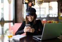 Stylish girl sitting at laptop and browsing smartphone — Stock Photo