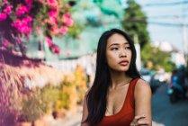 Молодая женщина в красном платье идет по улице и смотрит в сторону — стоковое фото
