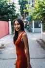 Mujer alegre en vestido rojo posando en la calle - foto de stock