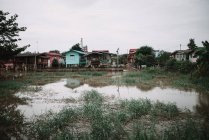 View to big puddle and small colorful rural houses in cloudy day. — Stock Photo
