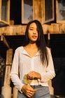Вродлива жінка позує біля будинку і дивлячись на камеру — стокове фото