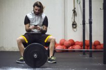 Sportivi che si siede sul bilanciere e navigazione smartphone in palestra. — Foto stock